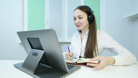 Young business woman with headphones carries a meeting on the video call.