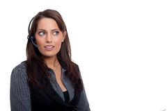 A young business woman with a headset. A woman wearing a business dress. Having a headset Royalty Free Stock Photography