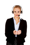 Young business woman in headset holding copyspace or something Royalty Free Stock Photos
