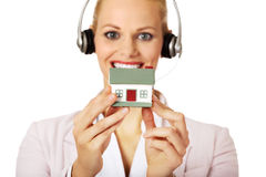 Young business woman in headset holding house model Royalty Free Stock Photo