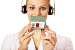 Young business woman in headset holding house model Royalty Free Stock Images