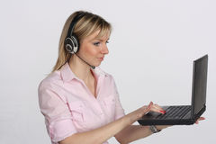 Young business woman with headset and laptop Royalty Free Stock Images