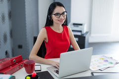 Young business woman in a headset works at a laptop in the office Stock Photos