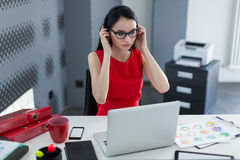 Young business woman in a headset works at a laptop in the office Royalty Free Stock Images