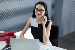 Young business woman in a headset works at a laptop in the office Royalty Free Stock Photos