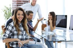 Young business woman and her creative team. Young business women and her creative team are sitting at your Desk Stock Images