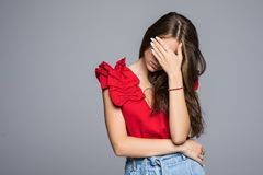 Young woman hides her face isolated on a gray background royalty free stock photography