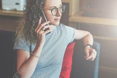 Young business woman hipster in glasses is sitting on sofa in office and talking on cell phone. Telephone conversations. Girl is waiting for business partner royalty free stock image