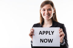 Young business woman holding an apply now sign Stock Photography