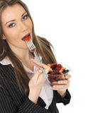 Young Business Woman Holding a Bowl of Fresh Mixed Berries Eating a Strawberry from a Fork Stock Photography