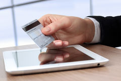 Young business woman  holding  a credit card . On-line shopping. On the internet using a tablet Stock Photography