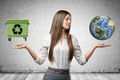 Young business woman holding earth globe and green trash can in her hands on grey wall background royalty free stock photography