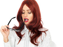Young Business Woman Holding Glasses in Her Mouth Looking Concerned and Attentive. Attractive Young Business Woman, with long red hair in her twenties holding stock images