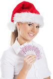 Young business woman holding money in santa hat. Royalty Free Stock Image