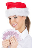 Young business woman holding money in santa hat. Royalty Free Stock Photos