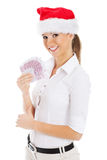 Young business woman holding money in santa hat. Royalty Free Stock Images