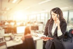 Young business woman holding notepad and talking on mobile phone royalty free stock image