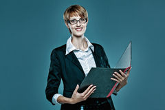 Young business woman holding an open folder and smiling to the camera Stock Photos