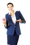 Young business woman holding piggy- bank. Isolated on white Royalty Free Stock Photos