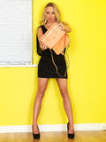 Young Business Woman Holding a Pink Handbag. A DSLR royalty free image, of an attractive young woman with blonde hair, holding an empty handbag upside down Stock Photo