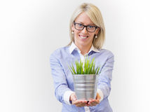 Young business woman holding pot with decorative green grass Royalty Free Stock Photography