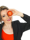 Young Business Woman Holding a Raw Tomato Royalty Free Stock Image