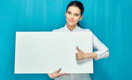 Young business woman holding sign board shows thumb. Up. Isolated blue back royalty free stock photo