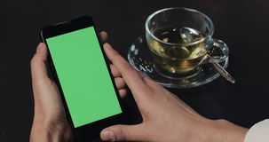 Young business woman holding smartphone with green screen close up in cafe stock footage