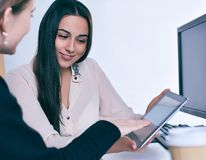 Young business woman holding tablet and discussing certain case with her colleague. Partnership agreement idea discussion, startup concept. Young business women Stock Image