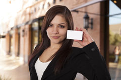 Young business woman holds up a blank business card. Royalty Free Stock Photography