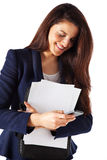 Beautiful businesswoman with papers and sending a message on smartphone Stock Image