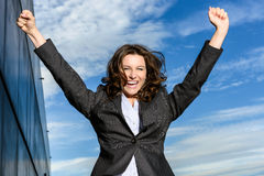 Young Business Woman is jumping for joy in front of blue cloudy sky. With office block to the side Royalty Free Stock Images