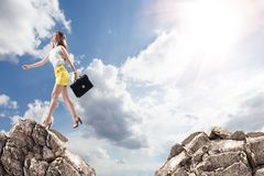 Businesswoman jumping on mountains. Young business woman jumping from the stone to another over blue sky background Stock Image