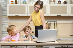 Young business woman in kitchen with her little Stock Photos