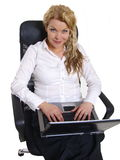 Young business woman with laptop. Young business woman sitting in a chair with a laptop Royalty Free Stock Images