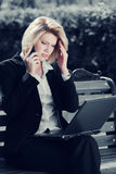 Young business woman with laptop calling on cell phone. In city park Royalty Free Stock Image