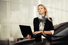 Young business woman with laptop on the car parkin Royalty Free Stock Photo