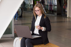 Young business woman with a laptop drinking coffee Stock Image