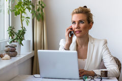 Young business woman with laptop in the office talking on a cell phone. Royalty Free Stock Photos