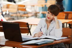 Young business woman with laptop at sidewalk cafe Royalty Free Stock Photo