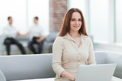 Young business woman with laptop sitting in the lobby of the business center. People and technology royalty free stock images