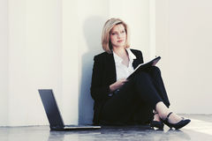 Young business woman with laptop sitting at office building Royalty Free Stock Photos