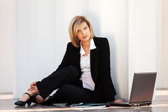 Young business woman with laptop sitting at the wall Royalty Free Stock Photo