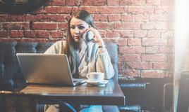 Young business woman with long hair sits at table in cafe and using laptop while talking on cell phone. Royalty Free Stock Photo