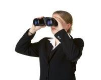Young business woman looking through binoculars Stock Photo