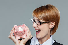 Young business woman looking at her piggy bank Stock Image