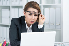 Young business woman looking intently at laptop. Monitor seeing something unusual Royalty Free Stock Images