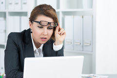 Young business woman looking intently at laptop. Monitor seeing something unusual Stock Photography