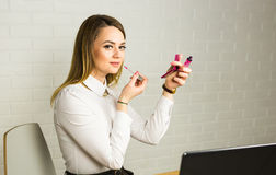 Young business woman looking in the mirror and using lipstick at her worlplace Royalty Free Stock Image