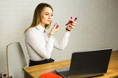 Young business woman looking in the mirror and using lipstick at her worlplace. Stock Photography
